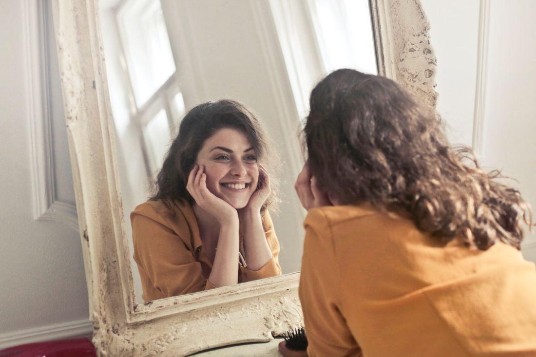 kobieta patrzy w lustro i uśmiecha się do siebie